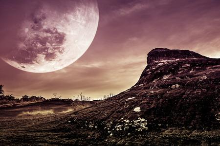 Landscape of rock with night sky and big moon above wilderness area in forest. It largest also called supermoon. Serenity nature background. Outdoor at nighttime. The moon taken with my own camera. Stock Photo