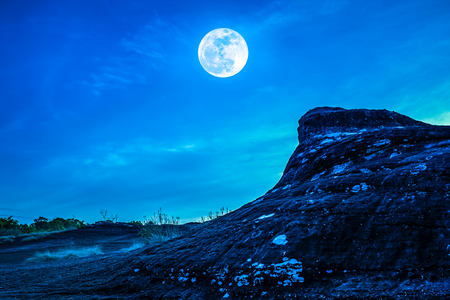 Landscape of the rock against blue sky and bright full moon above wilderness area in forest. Serenity nature background. Outdoor at nighttime. The moon taken with my own camera.