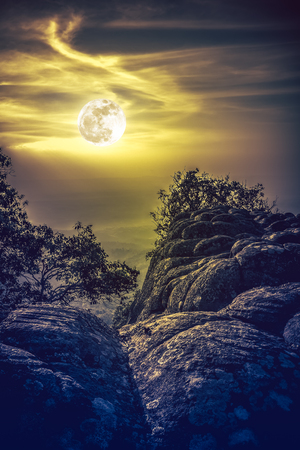Landscape of yellow sky with beautiful bright  full moon above view point on the top of mountain, serenity nature background. The moon taken with my own camera.