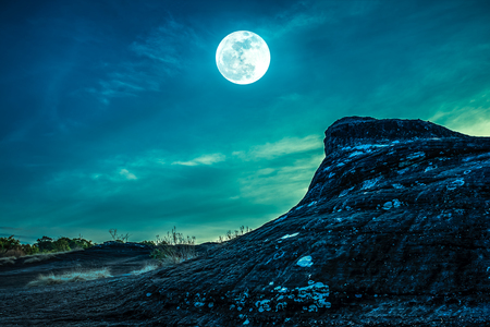 Landscape of the rock against night sky and bright full moon above wilderness area in forest. Serenity nature background. Outdoor at nighttime. Cross Process. The moon taken with my own camera. Stock Photo