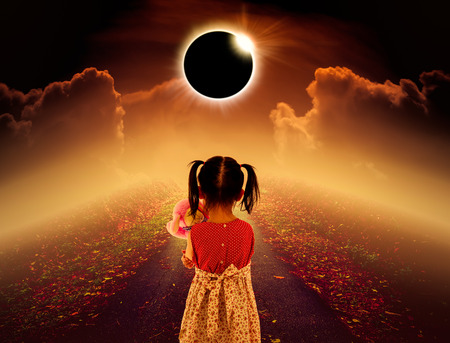 natural phenomenon: Amazing scientific natural phenomenon. Back view of child looking at total solar eclipse glowing on pathway with dark orange sky and clouds. Sepia tone.