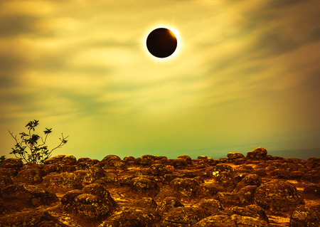 Amazing scientific natural phenomenon. Total solar eclipse with diamond ring effect glowing on sky above wilderness area. Abstract fantastic background of beautiful nature and serenity landscape.