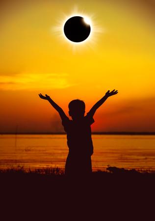 Geweldig wetenschappelijk natuurverschijnsel. Silhouet van kind die totale zonneverduistering met diamantring bekijken gloeiend op gouden hemel bij kust. Jongen die van mening geniet en zijn handen opheft. Stockfoto