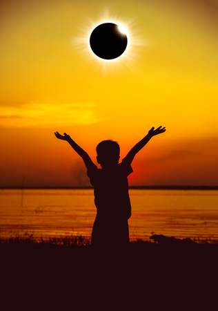 Amazing scientific natural phenomenon. Silhouette of child looking at total solar eclipse with diamond ring glowing on golden sky at seaside. Boy enjoying view and raising his hands up.