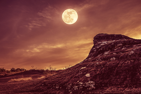Landscape of rock against night sky and bright full moon above wilderness area in forest. Serenity nature background. Outdoor at nighttime. Vintage effect tone. The moon taken with my own camera.
