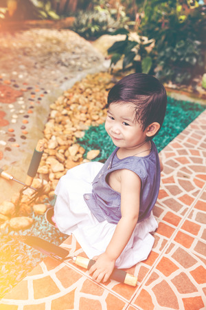 Adorable asian child with gardening equipment. Cute happy girl smiling and having fun in the garden at home. Concept about outdoors for children on summer day with bright sunlight. Vintage tone.