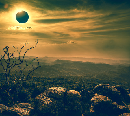 Amazing scientific natural phenomenon. The Moon covering the Sun. Total solar eclipse with diamond ring effect glowing on sky above wilderness area with mountain range. Serenity nature background. Stock Photo