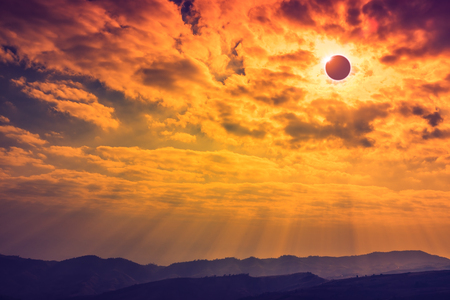 Amazing scientific natural phenomenon. The Moon covering the Sun. Total solar eclipse with diamond ring effect glowing on sky above mountain range. Serenity nature background.