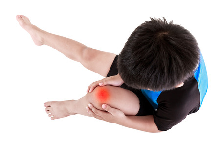 Sports injure. Top view of asian child cyclist injured at knee. Boy sitting and looking at bruise, isolated on white background. Human health care and problem concept. Studio shot. Stock Photo
