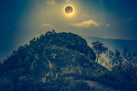 Amazing scientific natural phenomenon. The Moon covering the Sun. Total solar eclipse with diamond ring effect glowing on sky above view point on the top of mountain, serenity nature in forest. Cross