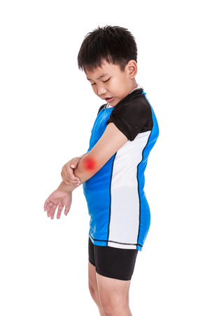 Conceptual of injure from sport. Asian child cyclist injured at elbow. Sad boy looking at bruise with a painful gesture, red spot indicating of pain. Isolated on white background. Studio shot.
