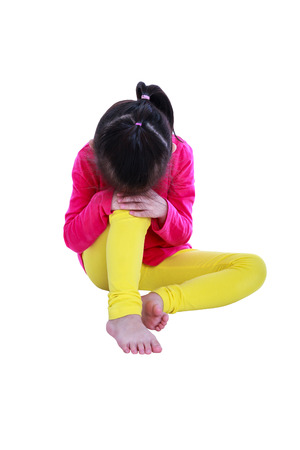 Lonely asian girl barefoot sitting on floor and sad gesture. Isolated on white background. Negative human emotions. Conceptual about children who lack warmth and affection, abandoned children. Stock Photo