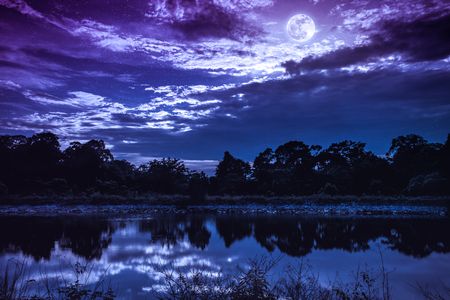 Landscape of colorful sky with many stars and dark cloudy. Full moon above  silhouettes of trees and lake. Serenity nature in gloaming time. The moon taken with my own camera.