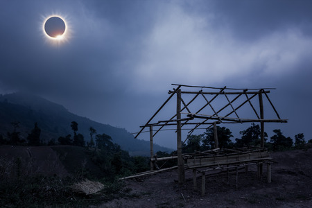 Amazing scientific natural phenomenon. The Moon covering the Sun. Total solar eclipse with diamond ring effect glowing on blue sky above little bamboo hut and mountain range. Serenity nature background.
