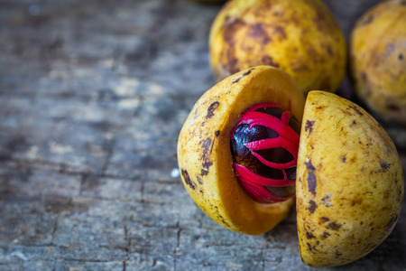 Pile of fresh nutmeg fruit with red placenta-like cover of seed of myristica fragrant, medicinal properties. Tropical colorful plant on wooden background with copy space.