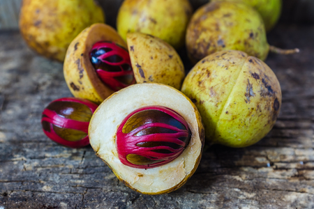Fresh nutmeg fruit with red placenta-like cover of seed of myristica fragrant, medicinal properties. Tropical colorful plant on wooden background.
