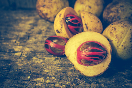 Pile of fresh nutmeg fruit with red placenta-like cover of seed of myristica fragrant, medicinal properties. Tropical colorful plant on wooden background. Vintage effect tone.