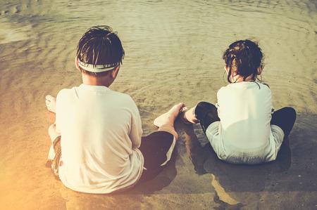 Achtermening van het Aziatische broer en zuster spelen met zand. Geluk broers en zussen genieten op het strand. Buitenshuis met zonlicht op zomerdag. Concept van het verbinden van kinderen met de natuur. Reis op vakantie.