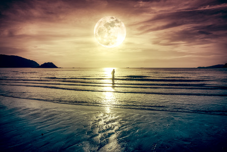 gloaming: Super moon. Colorful sky with bright full moon over seascape and silhouette of woman standing in the sea . Serenity nature background, outdoor at gloaming. The moon taken with my own camera.