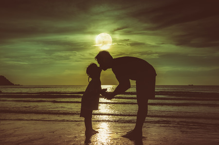 cute guy: Fathers day. Silhouette of loving child kissing her father. Family enjoying and relaxing on beach with full moon on sky background in the evening. Vintage effect tone. The moon taken with my own camera.