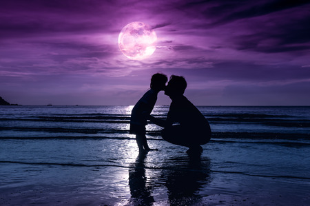 cute guy: Fathers day. Silhouette of loving child kissing her father. Family enjoying and relaxing on beach with full moon on purple sky background in the evening. The moon taken with my own camera.