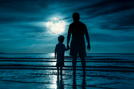 cute guy: Silhouette back view of loving child holding hands her father, standing in the sea. Family enjoying and relaxing on beach with full moon on green sky background. The moon taken with my own camera. Stock Photo