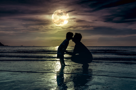 Fathers day. Silhouette of loving child kissing her father. Family enjoying and relaxing on beach with full moon on sky background in the evening. The moon taken with my own camera.