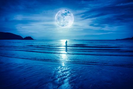 Super lune. Ciel bleu coloré avec pleine lune brillante sur paysage marin et la silhouette de la femme debout dans la mer. Fond de nature sérénité, en plein air au gloaming. La lune prise avec ma propre caméra.