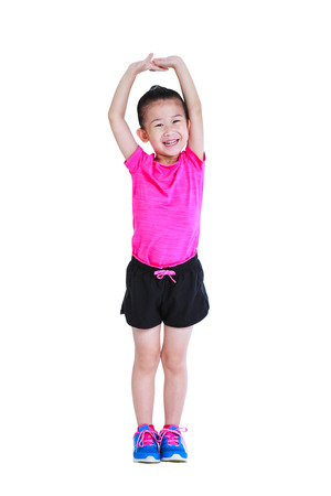 Full body of adorable asian child in sportswear doing exercise. Healthy chinese girl practicing fitness at studio. Sports and active lifestyle. Runner kid smiling happy isolated on white background.