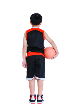 Back view of young asian basketball player in sportswear standing and posing with a ball in his hand. Studio shot. Isolated on white background.