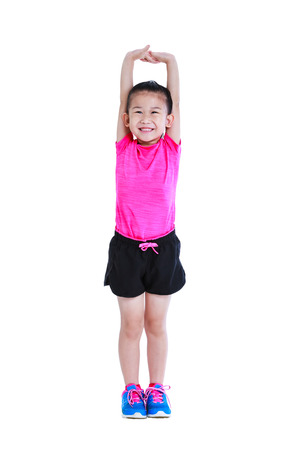 Full body of adorable asian child in sportswear stretching exercises. Chinese girl practicing fitness at studio. Sports and active lifestyle. Runner kid smiling happy isolated on white background.