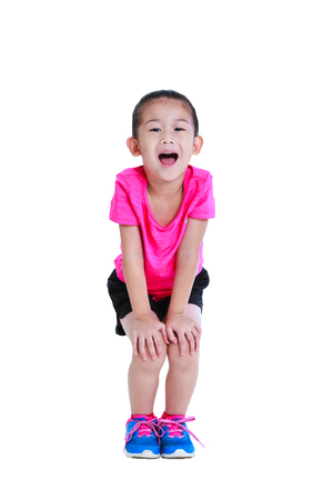 Adorable asian child in sportswear open the mouth with hands on her knees. Healthy chinese girl resting at studio. Sports and active lifestyle. Runner kid smiling happy isolated on white background.