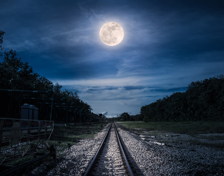 Railroad tracks through the woods at night. Beautiful blue sky and full moon above silhouettes of trees and railway. Serenity nature background. Outdoor at nighttime. The moon taken with my own camera