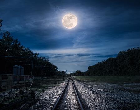 Vías del ferrocarril a través del bosque por la noche. Hermoso cielo azul y luna llena sobre siluetas de árboles y ferrocarril. Fondo de naturaleza serenidad. Al aire libre por la noche. La luna tomada con mi propia cámara. Foto de archivo