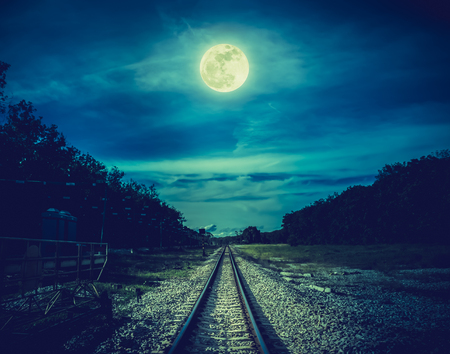 Railroad tracks through the woods at night. Beautiful sky and full moon above silhouettes of trees and railway. Serenity nature background. Outdoor at nighttime. The moon taken with my own camera