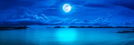 Hermosa vista panorámica del mar. Colorido cielo azul con nubes y brillante luna llena en el paisaje marino a la noche. Fondo de naturaleza serenidad, al aire libre en la noche. La luna tomada con mi propia cámara.