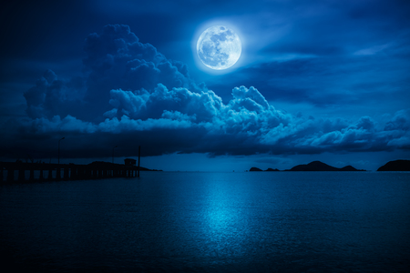 Beautiful landscape view of the sea. Colorful blue sky with clouds and bright full moon on seascape to night. Serenity nature background, outdoor at nighttime. The moon taken with my own camera. Stock Photo