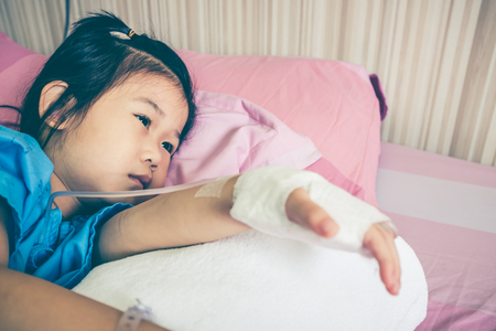 iv: Closeup illness asian child lying down on sickbed, admitted in hospital and saline intravenous (IV) drip on hand. Cute girl resting at recovery room. Health care stories. Vintage film filter effect.