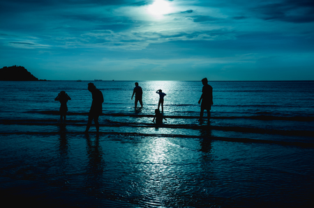 gloaming: Landscape of green sky with bright full moon over seascape and silhouette of six person standing in the sea. Family enjoying and relaxing on beach. Serenity nature background. The moon taken with my camera.