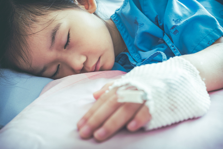 Closeup of illness asian child admitted in hospital with saline intravenous (IV) on hand. Girl sleeping at comfortable equipped hospital room. Health care stories. Vintage film filter effect.