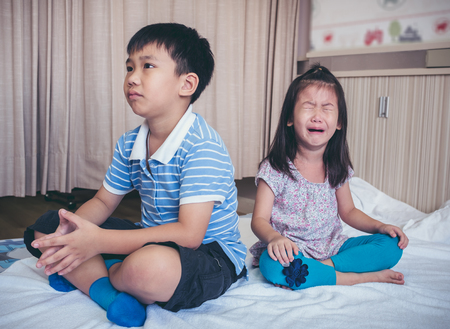 Quarreling conflict of children. Asian girl has problem between brother and scream crying with tears, sadden boy sitting near by. Relationship difficulties in family concept. Archivio Fotografico