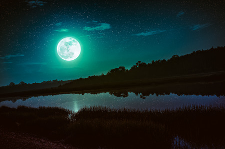 Beautiful landscape of emerald green sky with many stars and full moon above silhouettes of trees at riverside. Serenity nature background, outdoor at nighttime. The moon taken with my camera.