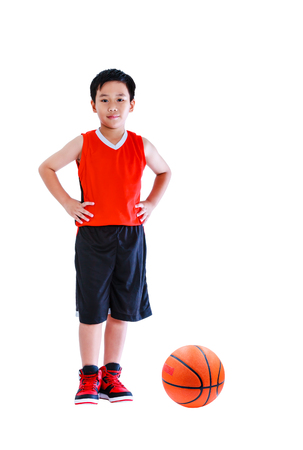 Full length of asian happy child in sportswear standing akimbo. Handsome boy smiling and looking at camera with a basketball at studio. Isolated on white background.