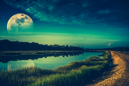 Beautiful landscape of green sky with cloud and fade half super moon above silhouettes of trees at riverside. Serenity nature background. Early evening outdoor. The moon taken with my camera. Stock Photo