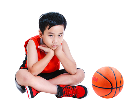 Unhappy asian child sitting near basketball.  Sad boy in sportswear propping up his head with hands and looking at camera. Studio shot. Isolated on white background.