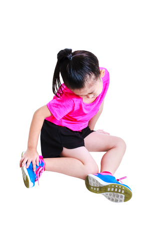 Sports injure. Full body of asian runner child  injured at ankle. Sad girl looking at bruise with a painful gesture, isolated on white background. Human health care and problem concept. Studio shot.
