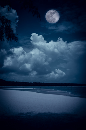 Beautiful landscape view on seascape to night. Attractive bright full moon on dark blue sky with cloudy. Serenity nature background, outdoors at nighttime. The moon taken with my own camera. Stock Photo