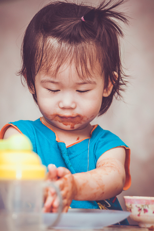 Portrait of a asian child enjoy eating. Her hand and mouth get stained with ketchup. Charming girl playing with food and learning to eat. Dirty face of happy kid. Do it yourself concept.