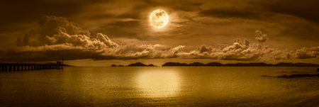 Panorama view of the sea. Colorful blue sky with cloud and bright full moon on seascape to night. Serenity nature background, outdoor at nighttime. Sepia tone. The moon taken with my own camera. Stock Photo
