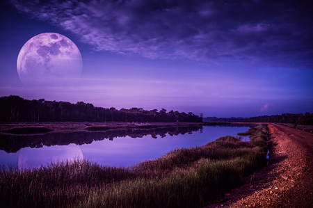Beautiful landscape of violet sky with cloud and fade half super moon above silhouettes of trees at riverside. Serenity nature background. Early evening outdoor. The moon taken with my camera. Stock Photo